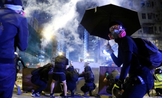 Protesters take cover behind boards during a protest in the Mong Kok area in Hong Kong