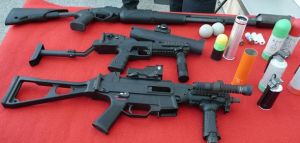 """From top to bottom: rifle of balls (launches rubber balls to long distances), GL-06 with the foldable ballistic helmet visor stock (launches ""ping pong"" balls softer and to a lesser distance), and a UMP submachine gun (9mm bullets) for roadblocks and raids"" by Galazan, Wikimedia"